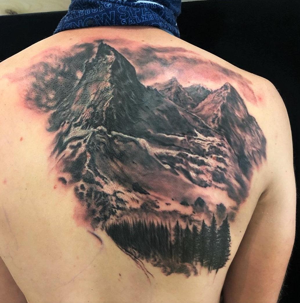 Tattoo Anansi München Artist Laszlo realism black and grey mountain Berge forrest Wald in progress