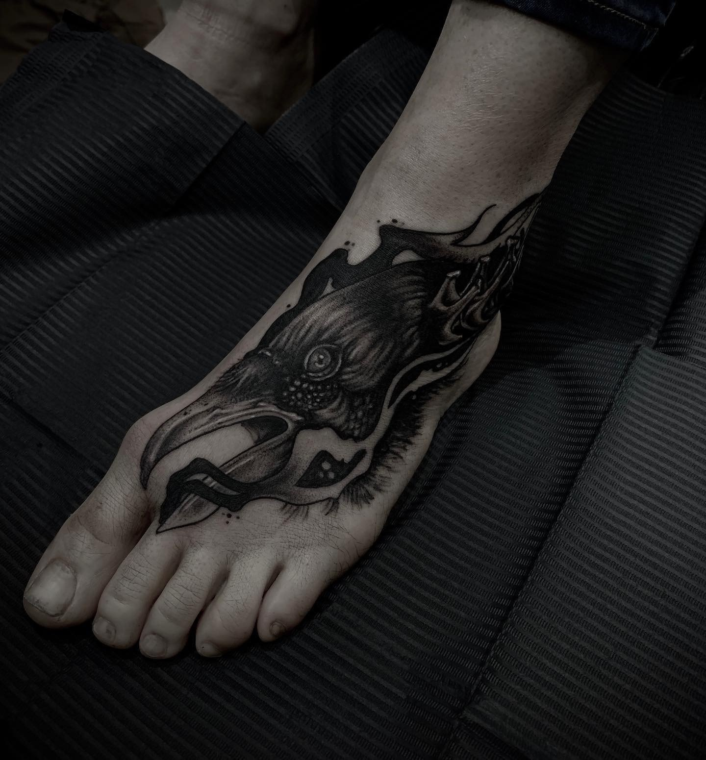 Tattoo Anansi München Artist David neotraditional black and grey raven Rabe foot